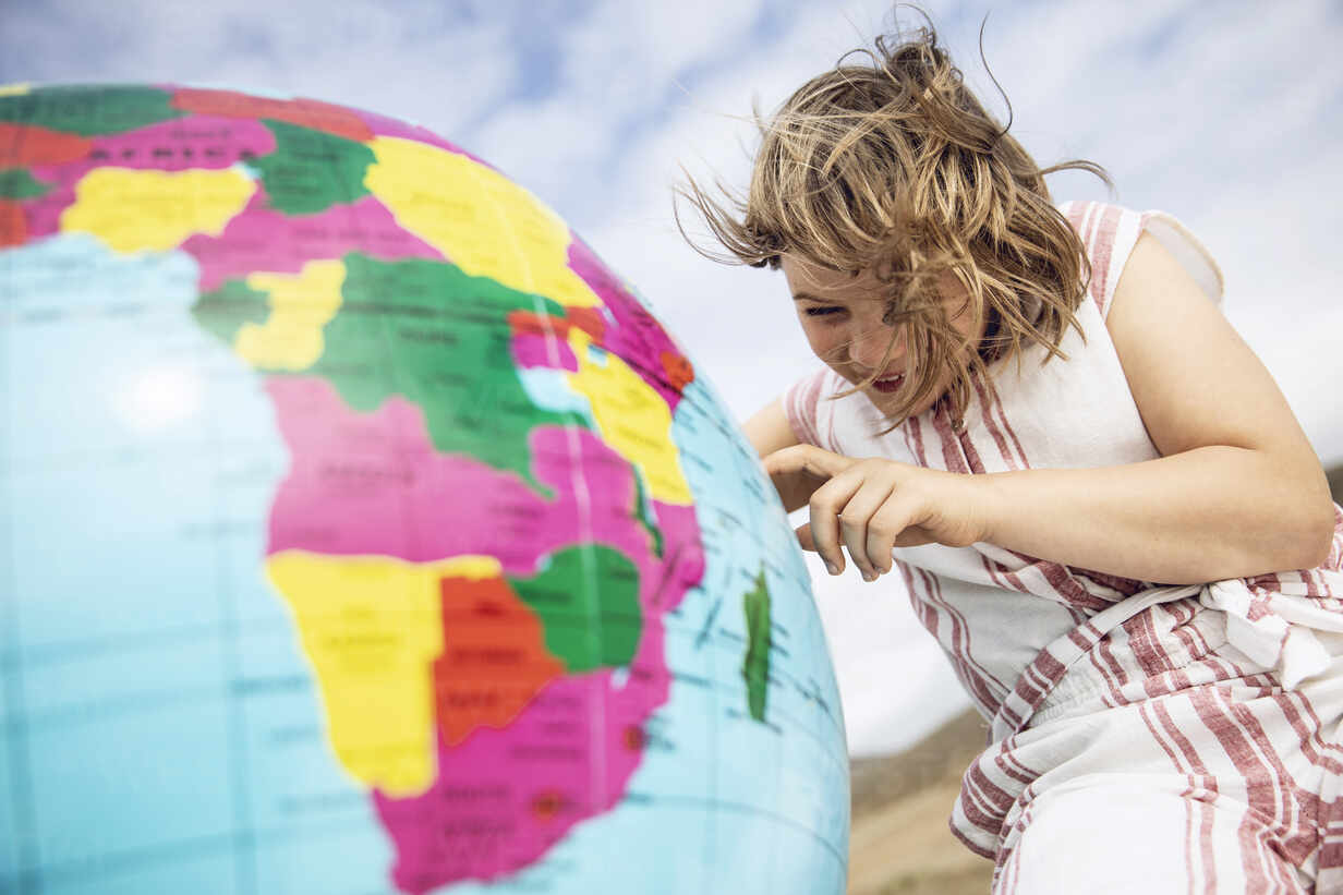 Little girl pointing on inflatable globe - MCF00524 - Maya Claussen/Westend61