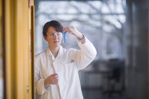 Female chemist at work examining a liquid - SGF02461