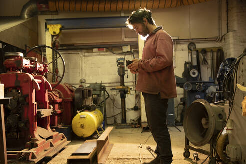 Metal worker working in workshop, using smartphone - PMF00917