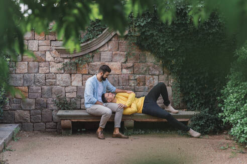 Gay couple relaxing together on a bench - AFVF04325