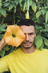 Portrait of man with blossom of angel's trumpet - AFVF04334