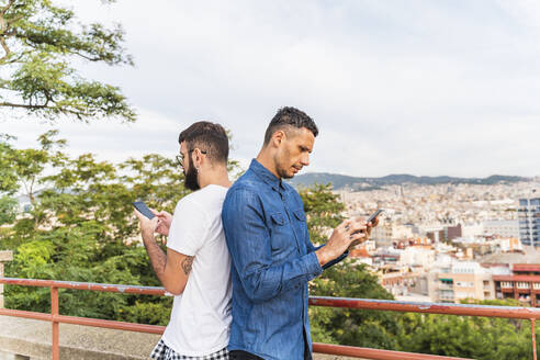 Gay couple standing back to back using smartphones, Barcelona, Spain - AFVF04340