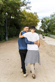 Back view of happy gay couple walking arm in arm in a park, Barcelona, Spain - AFVF04343