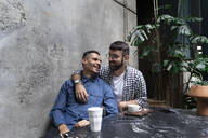 Gay couple relaxing together at outdoor cafe, Barcelona, Spain - AFVF04349