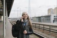 Portrait of happy young woman on the phone waiting on platform - AHSF01593