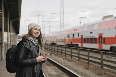 Portrait of smiling young woman with backpack and smartphone waiting on platform, Vilnius, Lithuania - AHSF01596