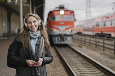 Portrait of happy woman standing on platform using smartphone and headphones, Vilnius, Lithuania - AHSF01599