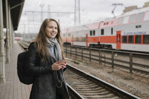 Smiling woman waiting on platform using smartphone and earphones, Vilnius, Lithuania - AHSF01602