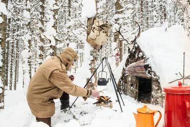 Man preparing tea in winter forest next to a wooden shelter, Salzburg State, Austria - HHF05582