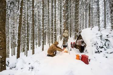 Man preparing tea in winter forest next to a wooden shelter, Salzburg State, Austria - HHF05585