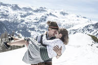 Happy couple kissing in the snowy mountains, Salzburg State, Austria - HHF05588