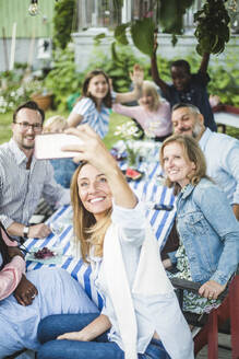 Woman taking selfie with family and friends at dining table in garden party - MASF14937
