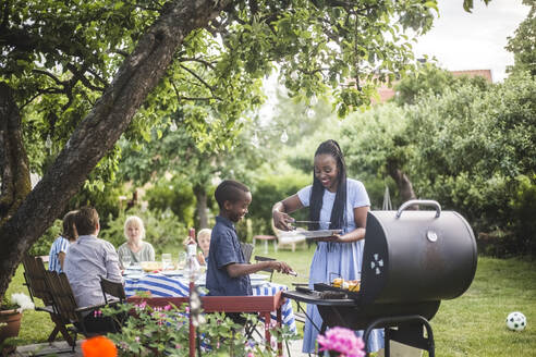 Smiling mother and son preparing food on barbecue grill together during backyard party - MASF14991