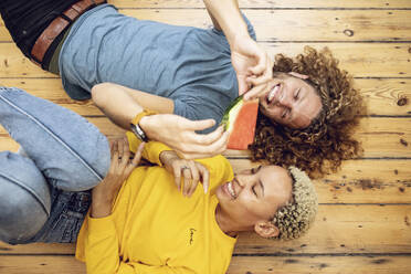 Happy young couple lying on the floor at home sharing a watermelon - MCF00530