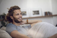 Smiling young man relaxing in beanbag at home - MCF00539
