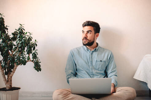 Man using laptop computer while sitting against wall on floor at home - CAVF69474