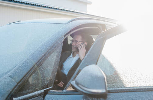 Man sat in his frosty car talking on the phone leaving for work - CAVF69582