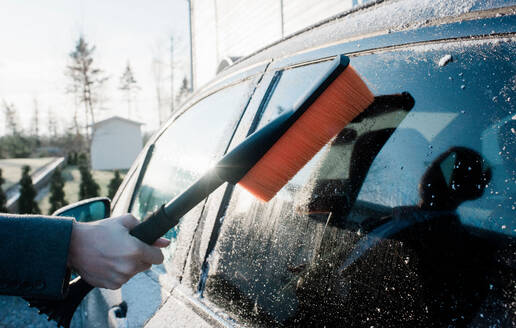 Mans hand brushing the frost away from his car in the morning - CAVF69585