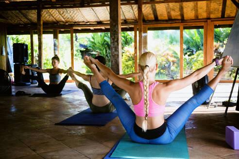 Friends practicing Pilates open leg rocker pose in yoga studio - CAVF69654