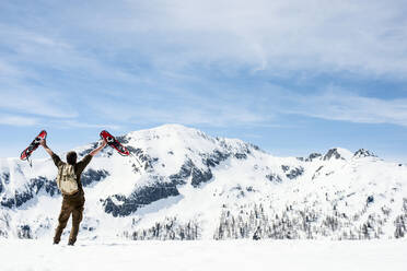 Man with backpack, standing on mountain summit, waving with his snowshoes, rear view, Salzburg State, Austria - HHF05592