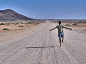 Man running freely on an endless road, rear view, Damaraland, Namibia - VEGF00999