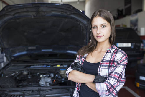 Casual woman in checkered shirt and gloves holding arms crossed and smiling at camera, working in car service - ABZF02861