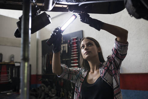 Brunette woman in shirt holding burning lamp and working with car standing under bottom in car repair shop - ABZF02867