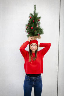 Woman wearing red pullover and wolly hat, holding artificial Christmas tree on top of her head, in front of a wall - HMEF00689