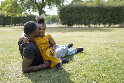 Affectionate father and daughter relaxing on a meadow in a park - FBAF00994