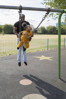 Father with happy daughter swinging on a playground - FBAF01015