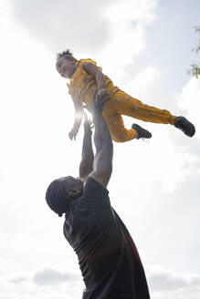 Father throwing happy daughter in the air - FBAF01021