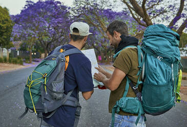 Two backpackers checking a map on a street - VEGF01018