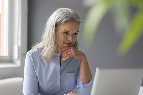 Portrait of mature businesswoman using laptop in office - MOEF02652