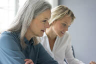 Portrait of two focused businesswomen working together in office - MOEF02658