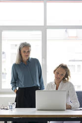 Two businesswomen using laptop at desk in office together - MOEF02664