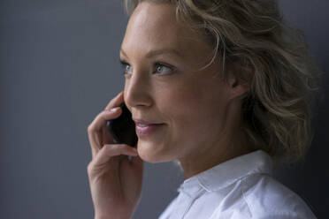 Portrait of smiling young businesswoman on the phone - MOEF02676