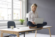 Smiling young businesswoman sitting on desk in office using laptop - MOEF02691