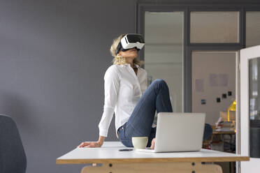 Young businesswoman sitting on desk in office wearing VR glasses - MOEF02694