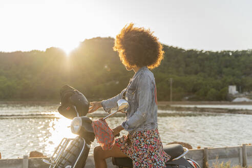 Young woman sitting on motor scooter during sunset, Ibiza - AFVF04355