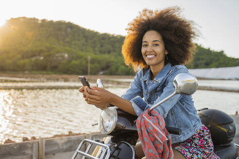 Young woman sitting riding on scooter and using smartphone at sunset, Ibiza - AFVF04361