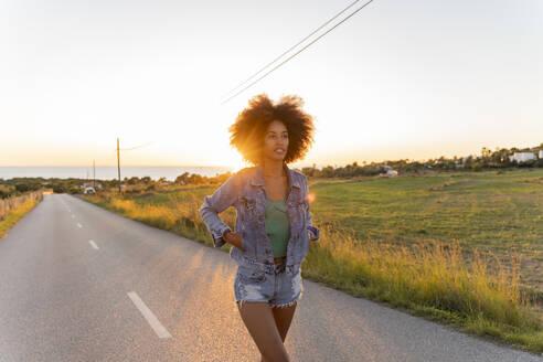 Young woman walking on street at sunset, Ibiza - AFVF04364