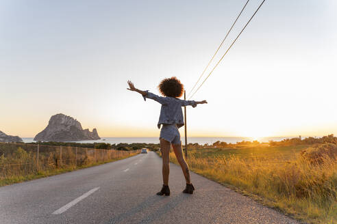 Young woman standing on street at sunset, Ibiza - AFVF04367