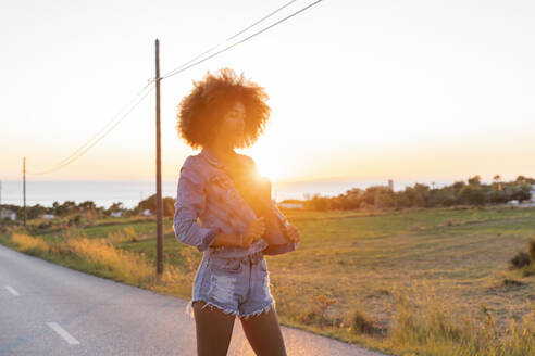 Young woman standing on street with closed eyes at sunset, Ibiza - AFVF04370