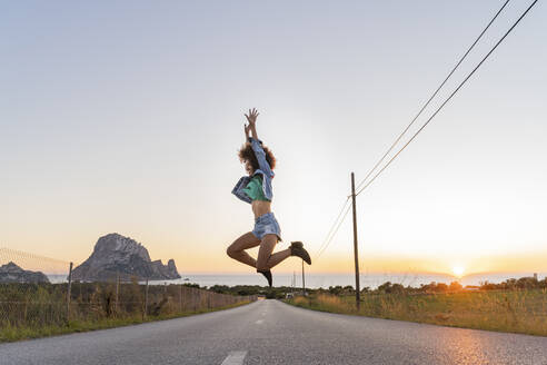 Young woman jumping on street at sunset, Ibiza - AFVF04373