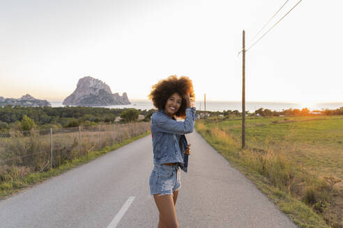 Young woman standing on street at sunset, Ibiza - AFVF04376