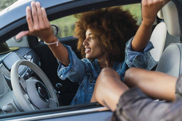 Young woman during road trip, sitting in car - AFVF04382