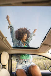 Young woman during road trip with raised arms - AFVF04388