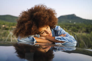 Young woman during road trip, leaning on car roof - AFVF04391