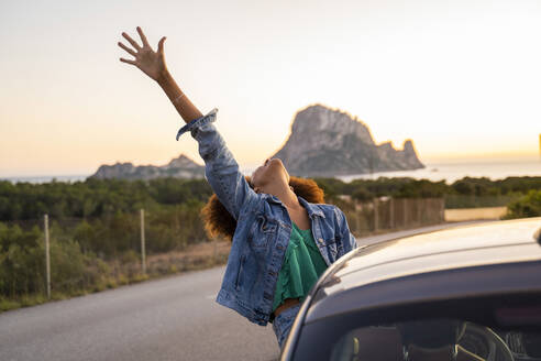 Young woman during road trip with raised arm - AFVF04394