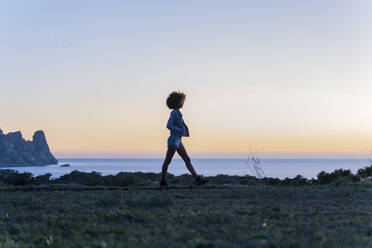 Young woman walking on a meadow at sunset, Ibiza - AFVF04400